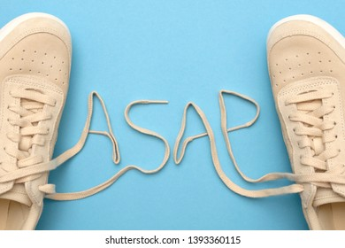 New women sneakers with laces in asap text abbreviation. As soon as possible. Flat lay on blue background.