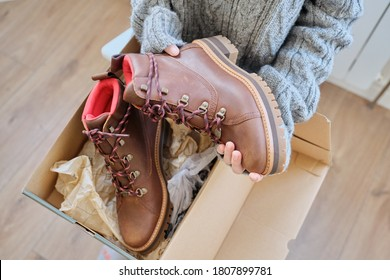 New womens leather brown waterproof hiking winter autumn boots in hands of female, trendy footwear for winter. Unpacking shoes, shopping online from home, shoe fashion store