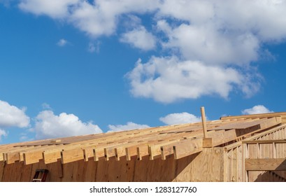 New wood frame construction. Blue sky, clouds. Room for text.