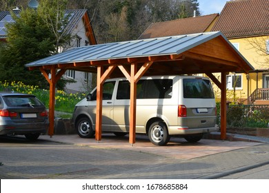 New wooden Carport with Standing Seam Metal Roof in Front of a Residential Building