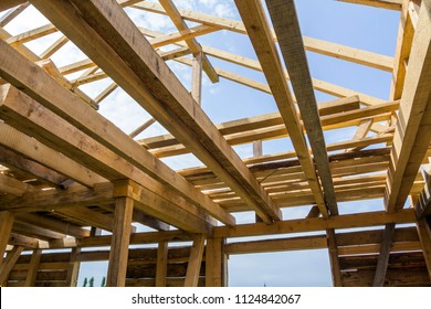 New wooden ecological house from natural materials under construction. Close-up detail of attic roof frame against clear sky from inside. Building, roofing, construction and renovation concept.
