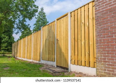 New wooden fence construction with stone wall and trees