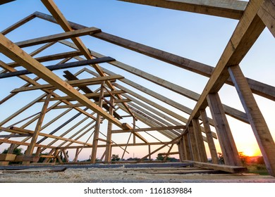 New wooden house under construction. Close-up of attic roof frame against clear sky from inside. Ecological dream home of natural materials. Building, construction and renovation concept.