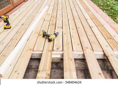 A new wooden, timber deck being constructed. it is partially completed. Two drills can be seen on the decking.