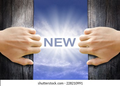 New word floating and shining in the sky while two hands opening an old wooden door.