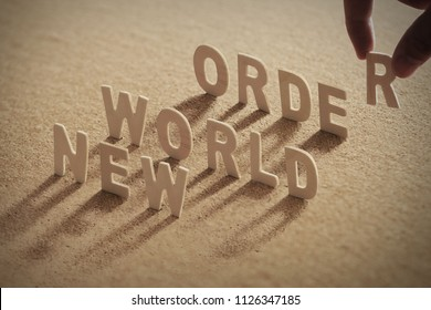 NEW WORLD ORDER wood word on compressed or corkboard with human's finger at T letter.