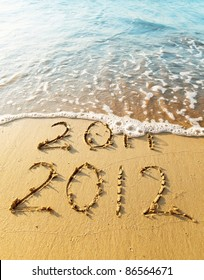 New Year 2012 is coming concept - inscription 2011 and 2012 on a beach sand, the wave is covering digits 2011.