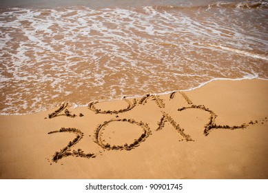 New Year 2012 is coming concept - inscription 2011 and 2012 on a beach sand, the wave is covering digits 2011