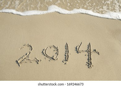 New Year 2014 is coming concept-New Year 2014 written in sand on the beach