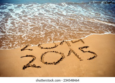 New Year 2015 is coming concept - inscription 2014 and 2015 on a beach sand, the wave is covering digits 2014