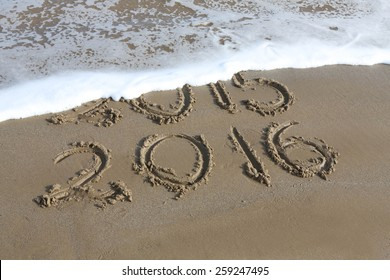 New Year 2016 is coming concept - inscription 2015 and 2016 on a beach sand, the wave is almost covering the digits 2015
