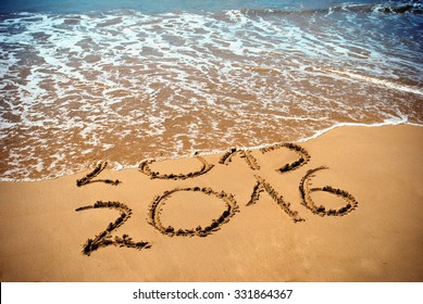 New Year 2016 is coming concept - inscription 2015 and 2016 on a beach sand, the wave is covering digits 2015