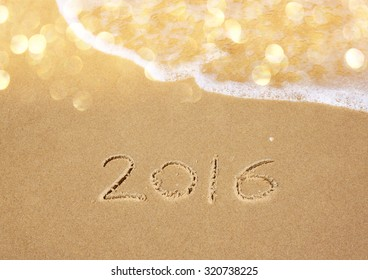 new year 2016 written in sandy beach. image is retro filtered
