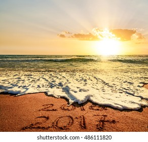 New Year 2017 is coming concept. Happy New Year 2017 replace 2016 concept on the sea beach at sunet