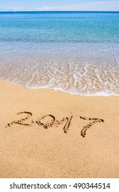 New Year 2017 is coming concept on the sandy beach with blue water and horizon