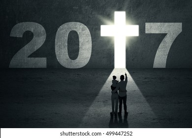 New Year 2017 is coming concept. Silhouette of a family looking at number 2017 with a bright cross symbol shaped a doorway