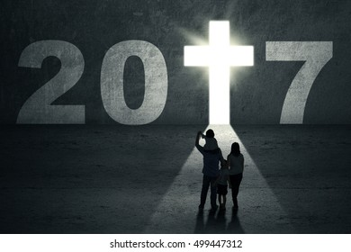 New Year 2017 is coming concept. Silhouette of a family looking at a doorway shaped a bright cross symbol with number 2017