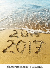 New Year 2017 is coming concept - inscription 2016 and 2017 on a beach sand, the wave is covering digits 2016.