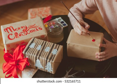 New year 2017 gifts boxes festive wrapping. hand lettering decorations. girl decorating gifts with handlettered calligraphy. handmade craft. Close up on hands. Wrapping inspiration. Christmas presents