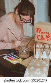 New year 2017 gifts boxes festive wrapping. hand lettering decorations. hot girl in glasses decorating gifts with handlettered calligraphy. handmade craft. Wrapping inspiration. Christmas presents