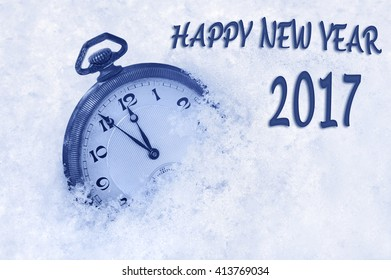 New Year 2017 greeting in English language, pocket watch in snow, happy new year 2017 text, 2017 new year concept