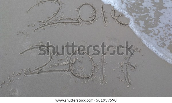 New Year 2017 replace 2016 on sea beach summer, New Year 2017 is coming concept. Closeup.
