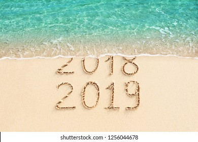 New Year 2018 change to 2019. Sand beach and blue ocean wave.