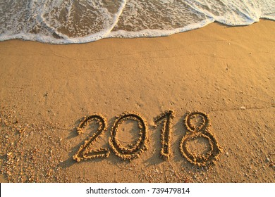 New Year 2018 is coming concept - inscription 2017 and 2018 on a beach sand, the wave is starting to cover the digits 2017