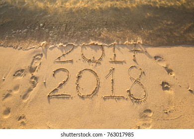 New Year 2018 is coming concept - inscription 2017 and 2018 on a beach sand, the wave is starting to cover the digits