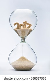 New Year 2018 concept. Time running out concept with hourglass falling sand from 2017.