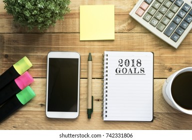 New Year 2018 Goals list written on a notepad with flat lay office desk and office supplies background.