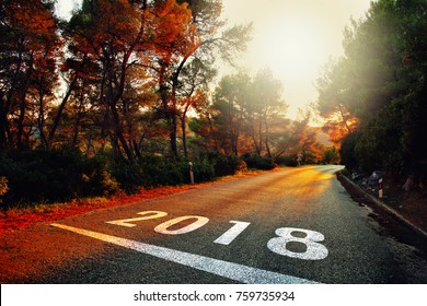 New Year 2018 number painted on colorful sunset asphalt road.