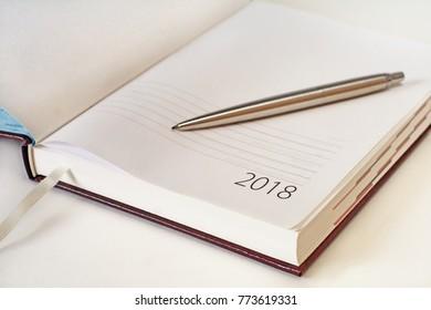 New Year 2018 office organizer calendar and sliver ballpen. Selective focus
