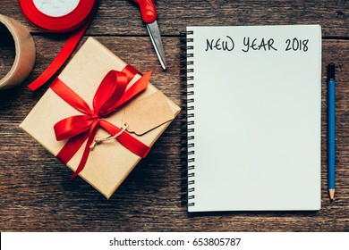 New Year 2018 on blank paper note book on wood table background.