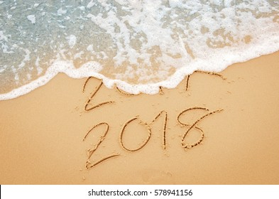 New Year 2018 replace 2017 on sea beach summer, New Year 2017 is coming concept. Closeup.