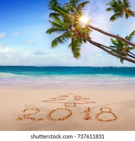 New Year 2018 written on sandy beach.