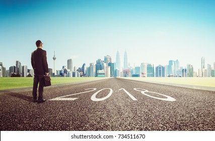New year 2018 ,young businessman looking on city skyline background . Determined to start concept .