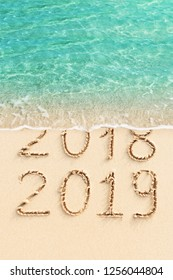 New Year 2019 celebration concept photo. 2018 and 2019 written on sandy beach with ocean wave.