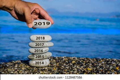 New Year 2019 is coming concept. Old year 2018 change to 2019. Turn of the year. Happy new year 2019 replace 2018. New hopes, ideas, excitement. Man adding pebble stone to tower. End of 2019