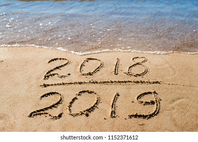 New Year 2019 is coming concept - inscription 2018 and 2019 on a beach sand, the wave is almost covering the digits 2018.