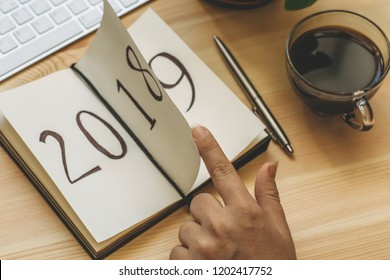 New Year 2019 is coming concept. Female hand flips notepad sheet with finger on wooden table. 2018 is turning, 2019 is opening, toned
