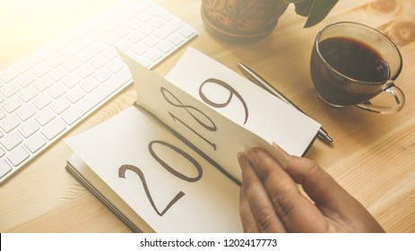 New Year 2019 is coming concept. Female hand flips notepad sheet on wooden table in sunlight. 2018 is turning, 2019 is opening, toned