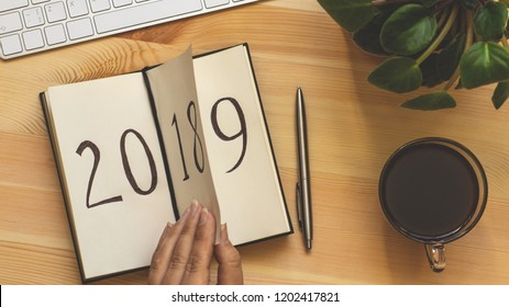 New Year 2019 is coming concept. Female hand flips notepad sheet on wooden table. 2018 is turning, 2019 is opening, top view, retro toned