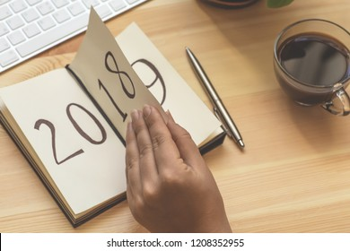 New Year 2019 is coming concept. Female hand flips notepad sheet on wooden table. 2018 is turning, 2019 is opening, toned