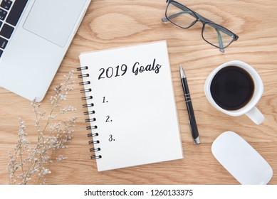 New year 2019 goals list in notebook with laptop, mouse, pen, glasses, green leaf, and coffee cup on wooden table background.