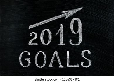 New Year 2019 goals with a rising arrow text chalk on a blackboard. Chalkboard written with text 2019 Goals. New year success in business. Plans for the year, increase in profits