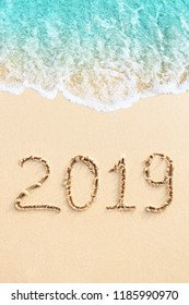 New Year 2019 handwritten on the sandy beach with ocean wave