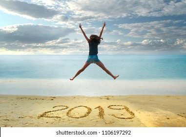 New Year 2019 on the sand,happy girl with hands up jumping on the beach