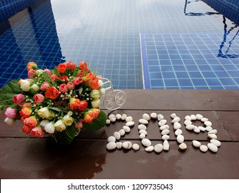 New year 2019 written by stones with artificial roses flowers on wooden background close up swimming pool
