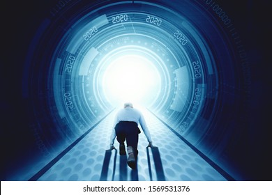 New Year 2020 business success concept: Back view of businessman in ready start running position in front of futuristic tunnel with number 2020
